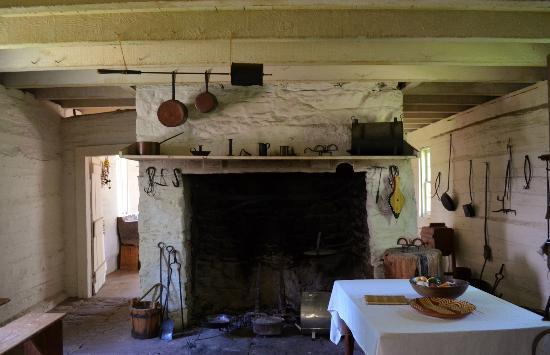 A picture of the kitchens at Sully Plantation in Virginia.  A big fireplace in the center of a small wood and stone room.